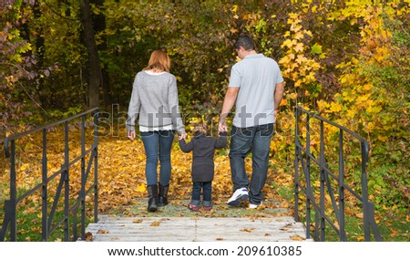 Happy young family in autumn making a walking tour in the nature. - stock photo