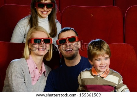 Happy young family in 3D glasses watching movie in cinema  - stock photo