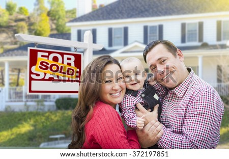Happy Young Family In Front of For Sale Real Estate Sign and House. - stock photo