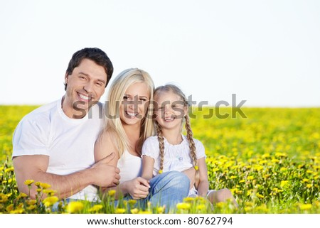 Happy young family in the field - stock photo