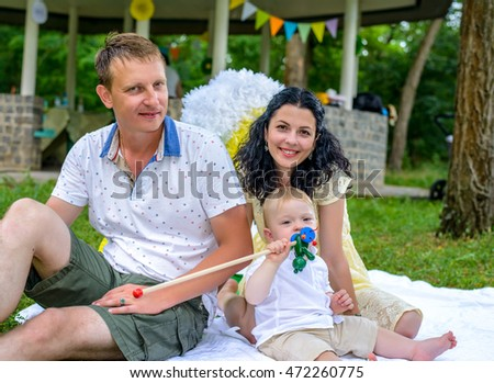 Happy young family in the park with their dog relaxing on a rug on the grass with their toddler son leaning affectionately towards each other and smiling at the camera