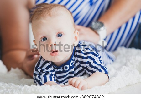Happy young family in the studio on a bright white background with a small child in striped shirts marine theme korblik inscription sea. - stock photo