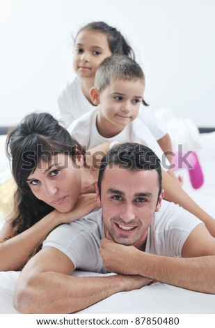 happy young Family in their bedroom have fun and play in bed