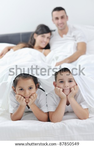 happy young Family in their bedroom have fun and play in bed - stock photo