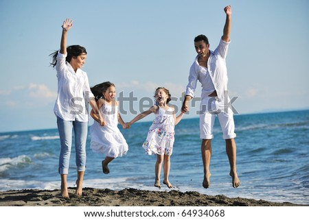 happy young family in white clothing have fun at vacations on beautiful beach