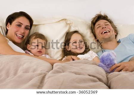 Happy young family laying in bed - stock photo