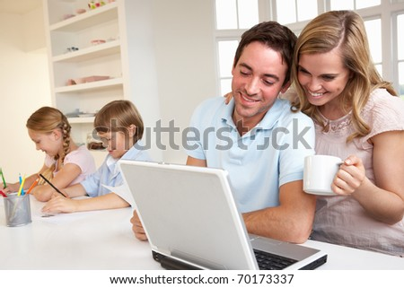 Happy young family looking and reading a laptop computer - stock photo