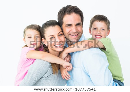 Happy young family looking at camera together on white background - stock photo