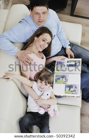 happy young family looking old pictures in photo album at home - stock photo