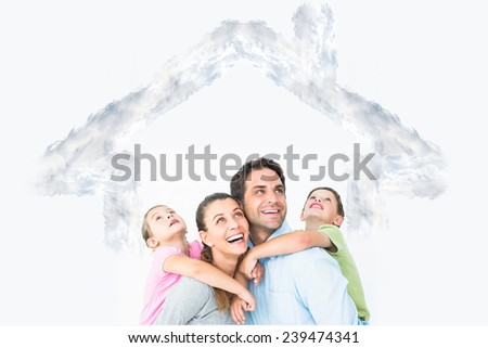 Happy young family looking up together against house outline in clouds - stock photo