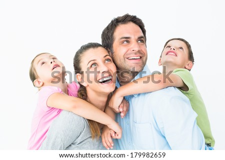 Happy young family looking up together on white background - stock photo