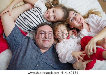 happy young family lying in bed - stock photo