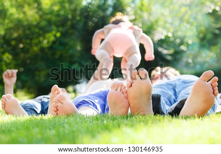 Happy young family lying on green grass outdoors in the summer park - stock photo