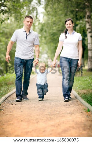 happy young family mom dad and baby in the park - stock photo
