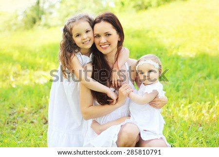 Happy young family, mother and two daughters childrens together having fun outdoors on the nature - stock photo
