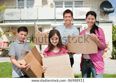 Happy young family moving into new home carrying boxes - stock photo