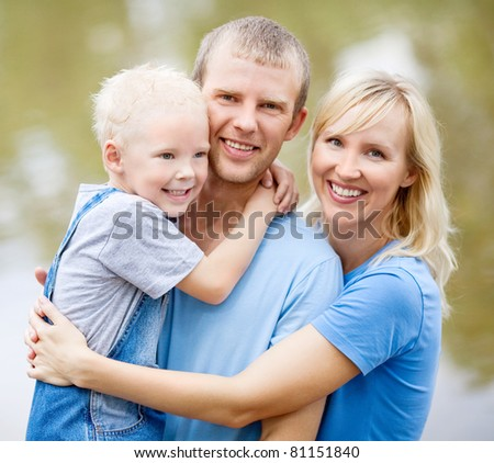 happy young family  near the lake outdoor on a summer day (focus on the child)