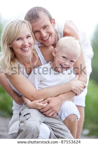 happy young family  near the lake outdoor on a summer day (focus on the woman) - stock photo