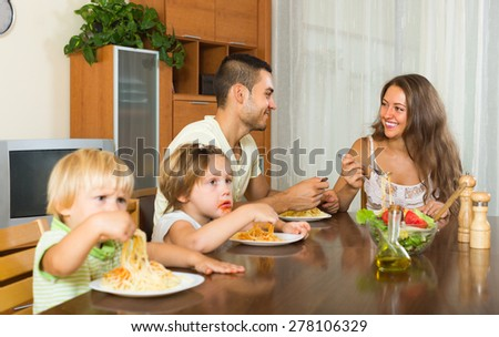 Happy young family of four eating with spaghetti at table - stock photo
