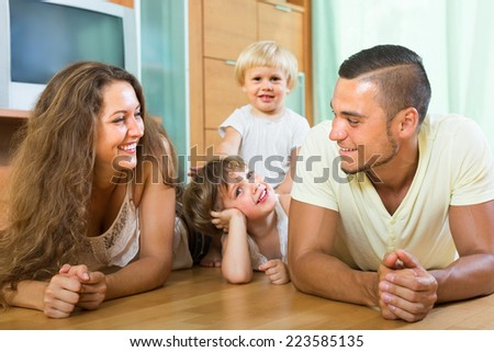 Happy young family of four enjoying time in living room at their home  - stock photo