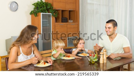 Happy young family of four having lunch with spaghetti at home. Focus on woman  - stock photo