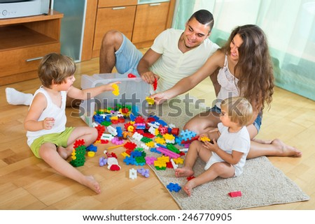 Happy young family of four relaxing at home with toys  - stock photo