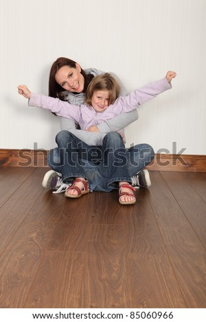 Happy young family of mum and daughter with hug and embrace sitting on the floor at home. Girl has arms raised celebrating success. Both wearing denim jeans and hoodie. - stock photo