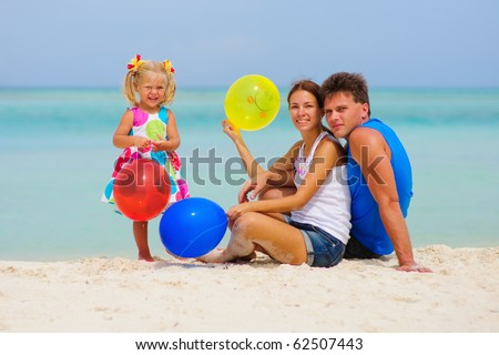 happy young family of three have a party with colorful balloons on tropical beach - stock photo