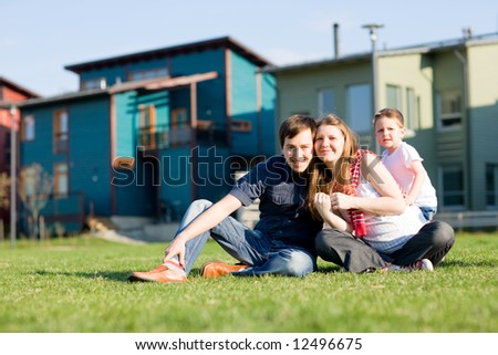 Happy young family of three having fun in front of theirs house at sunny day.