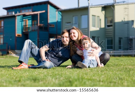 Happy young family of three having fun in front of theirs house at sunny day. - stock photo