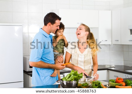 happy young family of three in home kitchen - stock photo