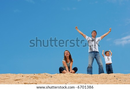 Happy young family of three on top of sand dune with blue-blue sky on background - stock photo
