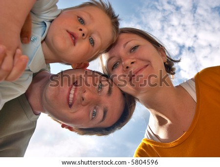Happy young family of three smiling to camera with blue sky on background