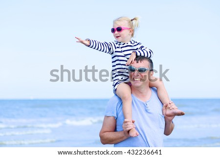 Happy young family of two playing on tropical exotic beach. Smiling father and his adorable little daughter having fun together and enjoying sunny summer day at the sea. - stock photo