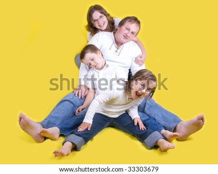 Happy young family on floor with mother, father, daughter and son - yellow background