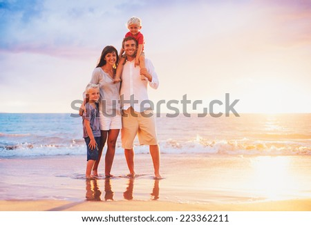 Happy Young Family on the Beach at Sunset - stock photo