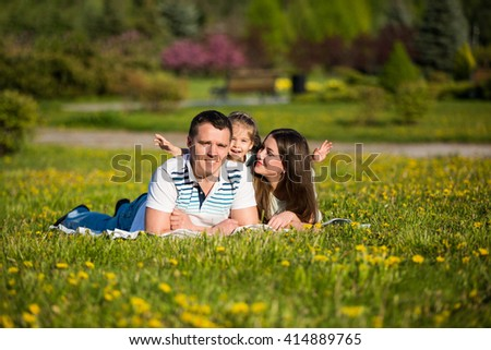 Happy young family on the perfect lawn dandelion flowers