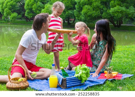 Happy young family picnicking outdoors