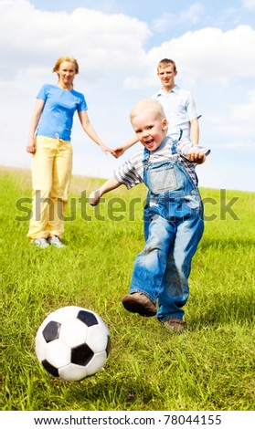happy young family playing football outdoor on a summer day - stock photo