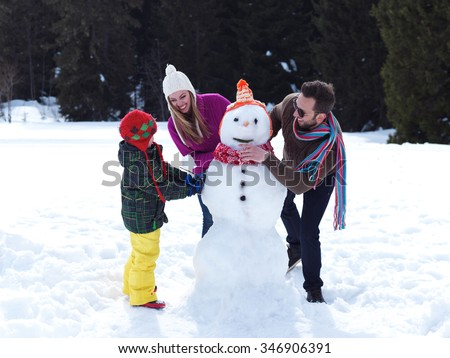 happy young  family playing in fresh snow and making snowman at beautiful sunny winter day outdoor in nature with forest in background - stock photo