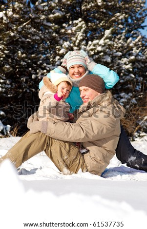 Happy young family playing in the snow - stock photo