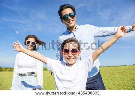 Happy young family playing on the grass - stock photo