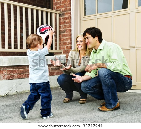 Happy young family playing soccer with toddler on driveway - stock photo