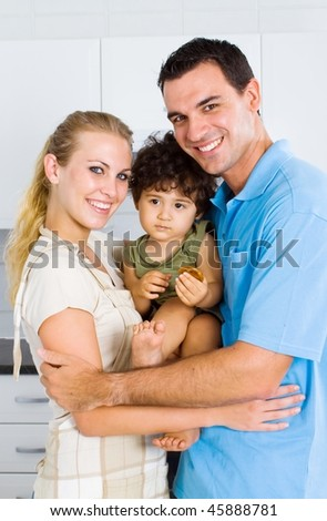 happy young family portrait in new kitchen