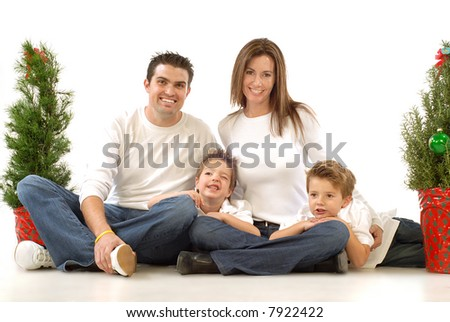 Happy young family posing for their cheerful holiday portrait - stock photo