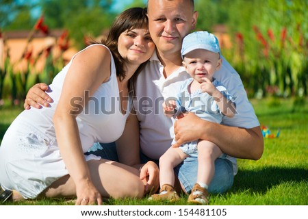 Happy young family posing on green grass at park - stock photo
