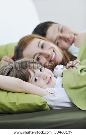 happy young family relaxing in bed - stock photo