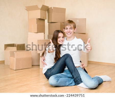 happy young family showing thumbs up on a background of cardboard