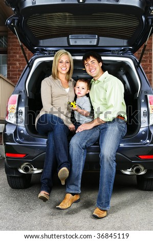 Happy young family sitting at back of car - stock photo