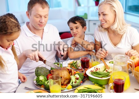 Happy young family sitting by festive table and eating traditional Thanksgiving food - stock photo